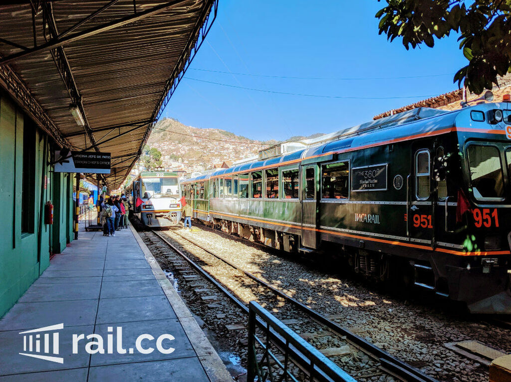 """PeruRail's """"Voyager"""" waiting on the platform next to IncaRail's """"360°-Train"""""""