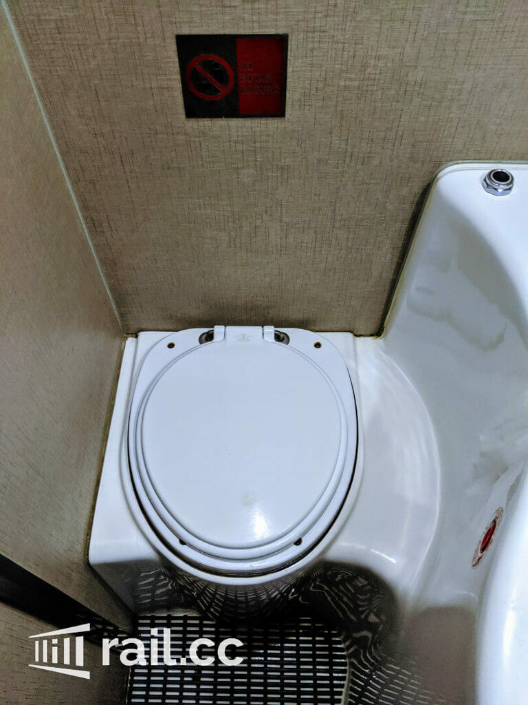 Toilet with black button to flush on the top right